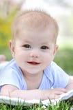 春天,草的愉快的微笑的婴孩 免版税库存图片