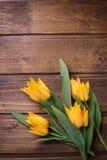 春天黄色郁金香在棕色木背景开花 库存图片