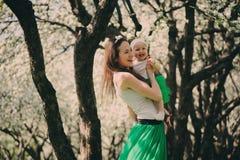 春天画象母亲和小女儿使用室外在配比的成套装备-长的裙子和衬衣 库存照片
