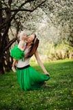 春天画象母亲和小女儿使用室外在配比的成套装备-长的裙子和衬衣 库存图片