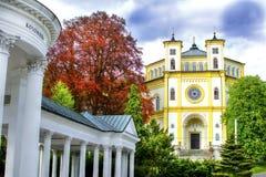 春天Karolina柱廊和天主教会在Marianske Lazne 图库摄影