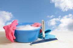 春季大扫除,有肥皂泡沫的蓝色塑料碗,变粉红色橡胶g 免版税库存照片