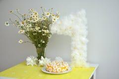 春黄菊花束和女孩的生日蛋糕1年 免版税库存照片