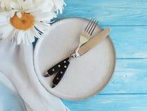 春黄菊,板材,叉子,在蓝色木背景的庆祝宴会言情晚餐夏天承办酒席 免版税库存图片