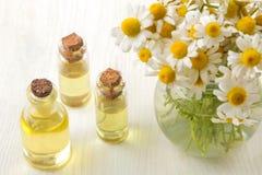 春黄菊 春黄菊医药小的花与芳香油的在一张白色木桌上 r 库存照片