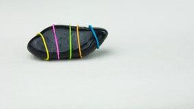 是与色的条纹的另外一块黑石头在明亮的背景 免版税库存照片