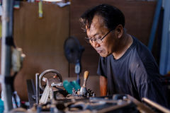 是亚洲人的工匠加工的钢在工厂 库存照片