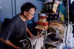 是亚洲人的工匠加工的钢在工厂 库存图片