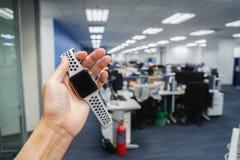 是准时概念-妇女举行巧妙的手表在办公室 图库摄影