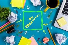 是创造性的词 办公室有供应的桌书桌,白色空白的笔记本,杯子,笔,个人计算机,弄皱了纸,在木的花 免版税图库摄影