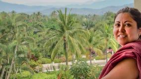 是在有棕榈树和山的一个阳台在背景中的美丽的墨西哥妇女 免版税库存照片