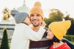 是宜人的看起来的小女孩感激的对她的买的新的自行车父亲,在面颊亲吻他 一起年轻家庭步行 图库摄影