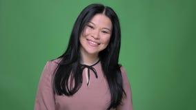 是年轻可爱的亚裔的女性特写镜头射击有黑色头发的微笑和害羞看直接照相机 股票视频