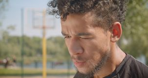 是年轻英俊的非裔美国人的男性的篮球运动员特写镜头画象疲乏坐户外 影视素材