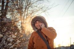 是微笑和谈话在电话在冬天冷的天在日落迷人的人的画象,黎明 免版税库存照片