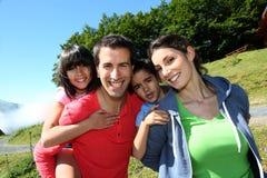 是微笑的家庭画象愉快的在山 库存照片