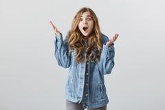 是您在您的头脑外面 震惊不耐烦的欧洲女朋友演播室射击有金发的在时髦的牛仔布夹克 免版税图库摄影
