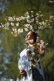 是愉快年轻很快母亲妈妈-年轻旅客孕妇在有开花的一个公园享受她的休闲时间 免版税库存照片