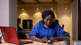 是成人非裔美国人的女实业家特写镜头射击使用膝上型计算机的检查在电话的通知和 影视素材