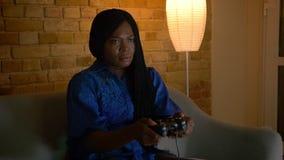 是成人非裔美国人的女性特写镜头射击打电子游戏和在长沙发的愉快的开会户内 股票录像