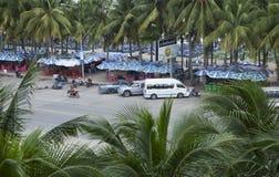是拉差海滩街道与许多椰子树的在边 免版税库存照片