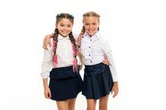 是明亮的 学校友谊 妇女团体关系和知己 在同样波浪 女小学生佩带正式学校 库存图片