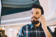 总是有联系 微笑的英俊的年轻人谈话在他的电话 库存图片