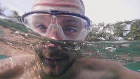 是潜水水下和游泳在热带海滩的面具享受他的假期的旅游人 E 股票视频