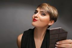 是灰色背景的一个真正的巧克力爱好者一名美丽的妇女的画象 免版税库存照片