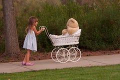 是白色柳条的一点推挤的玩具婴孩车 免版税库存照片