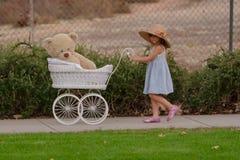 是白色柳条的一点推挤的玩具婴孩车 免版税库存图片