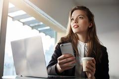 是的女孩创造性的,当组成新的岗位室内射击梦想的可爱的女性办公室工作者,坐在咖啡馆时 库存照片