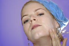 是秀丽的少妇应用的表面化妆水 免版税库存图片