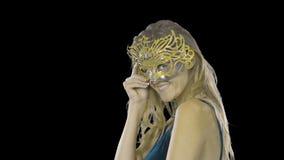 是穿戴和尝试在面具一名性感的妇女的画象,在一个党的威尼斯式化妆舞会狂欢节面具,在  影视素材