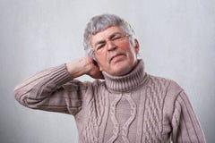 是老人佩带的玻璃照片疲乏从握他的在头的坚苦工作手 一个成熟人有头疼在工作以后 免版税图库摄影