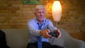 是老白种人businessmanplaying的电子游戏的失败特写镜头画象在长沙发的被挫败的开会户内 股票视频