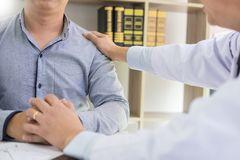 是被再保证的绝望举行的手由医生令人鼓舞支持和安慰与同情的患者 在医房 库存图片