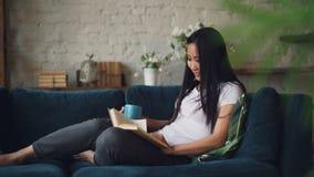 是阅读书享受滑稽可笑的故事和笑坐在舒适顶楼样式公寓的沙发的美丽的亚裔妇女和 股票视频