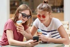 是高兴的满意的女性的伴侣现代手机被聚焦的ino屏幕,观看有趣录影网上,连接到wirel 免版税库存照片