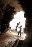 是年轻有吸引力的夫妇挥动和嬉戏的通过岩石拱道 免版税库存照片