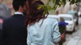 是年轻的夫妇少量射击步行沿着向下老城市街道在伞下,一起笑和愉快的 股票视频