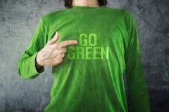 是绿色。供以人员指向在他的衬衣打印的标题 免版税图库摄影