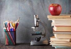 显微镜、铅笔、书和苹果 免版税图库摄影