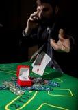 显示一个丢失的组合在啤牌卡片,人的打牌者喝从哀情的威士忌酒 免版税库存照片
