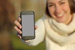 显示一个巧妙的电话屏幕的妇女在冬天户外 免版税库存图片