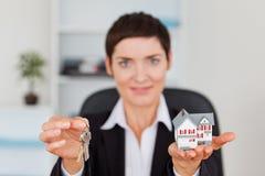 显示一个微型房子和关键字的妇女 免版税库存照片