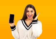 显示一个新的智能手机的白色毛线衣的惊奇的愉快的妇女 免版税库存图片