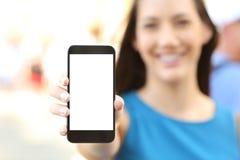 显示一个空白的垂直的电话屏幕的女性 库存图片