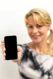 显示一个空白的手机的微笑的妇女 免版税库存照片