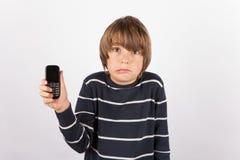 显示一个简单的电话的年轻男孩非常生气 免版税库存图片